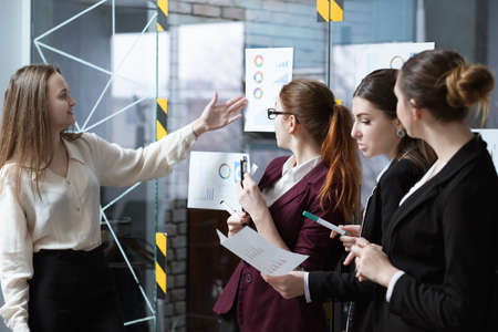 Business meeting. Successful corporate strategy presentation. Female speaker pointing at annual corporate statistics Stock Photo
