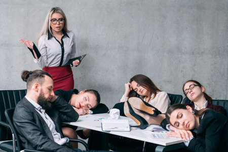 Overworking team. Annual business report. Astounded teamlead looking at colleagues sleeping at workplace.
