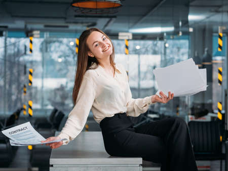 Successful negotiations. Corporate lawyer workplace. Smiling business female sitting on desk with contract. Zdjęcie Seryjne