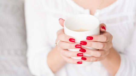 Coffee break. Relax time. Woman hands with red manicure hold white cup of latte.