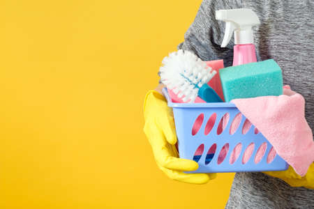 Housekeeping concept. Cleaning services. Torso with basket of cleanup supplies. Copy space on yellow background.