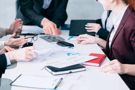 Análisis de venta. Reunión de negocios. Equipo exitoso analizando diagramas. Teamlead apuntando a documentos.