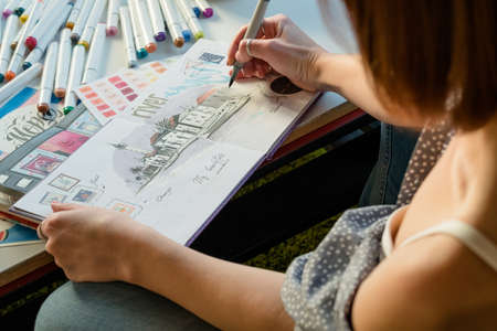 Artist sketching. Workplace inspiration. Woman painter drawing in sketchbook with palette and supplies around. Banco de Imagens - 118053513