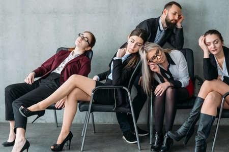 Corporate workaholics. Overworking. Business team members sleeping on workplace chairs. 写真素材
