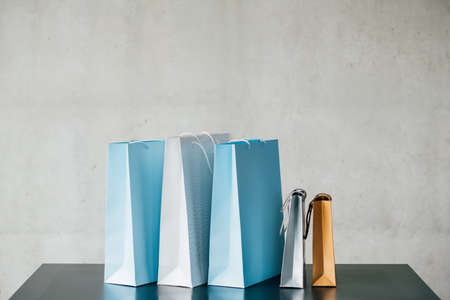 Its shopping time. Urban consumerism. Paper bags row on desk. Copy space on grey background.