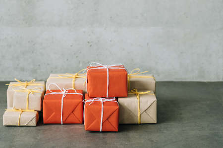 Online shopping. Delivery service. Parcel stack wrapped in red and craft paper. Copy space on grey background. Stock Photo