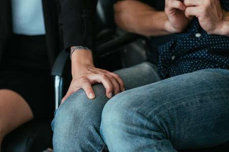 Empleador y empleado. Comportamiento de acoso. Mano de mujer de negocios en la rodilla del hombre subordinado. Foto de archivo