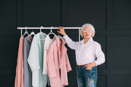 Senior fashion style. Shopping experience. Elderly lady looking at camera while choosing outfit. 스톡 콘텐츠
