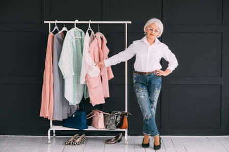 Senior lifestyle. Fashion clothes shopping. Confident elderly lady showing stylish wardrobe. 스톡 콘텐츠