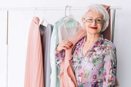 Senior lady wardrobe. Shopping and clothing options. Smiling elderly woman choosing trendy outfit.