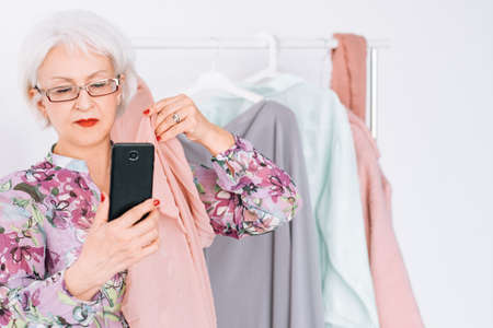 Senior fashion stylist at work. Successful business lady. Elderly female taking selfie. Personalized shopping service. 写真素材
