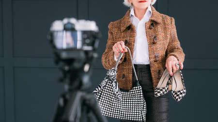 Senior fashion blogger. Bag and shoes review. Aged stylish lady shooting vlog.