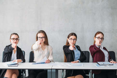 We choose you. Human resources team. Pretty females pointing at virtual applicant. Copy space on grey background. Stock Photo