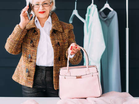 Senior fashion model. Modern lady lifestyle. Stylish aged woman with smartphone in autumn outfit posing for photo shoot. Фото со стока