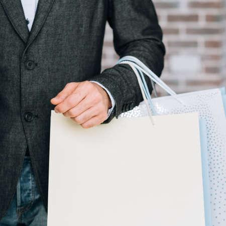 Fashion clothing shopping. Season store discount. Man with mockup paper bag.