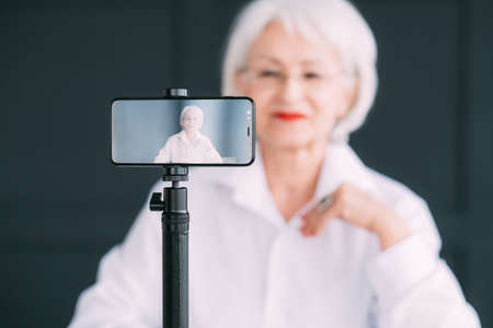 Senior business lady blogger. Financial independence and personal development. Elderly woman making video tutorial. Stock Photo