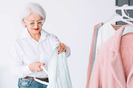 Smart senior lady wardrobe. Shopping leisure. Personal style of wealthy elderly woman.
