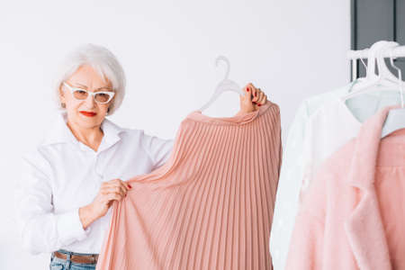Senior fashion trends. Personal style. Confident elderly woman demonstrating clothing option. 스톡 콘텐츠