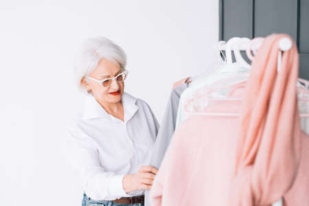 Senior fashion. Stylish showroom. Smart elderly lady in glasses looking through rack of clothing.