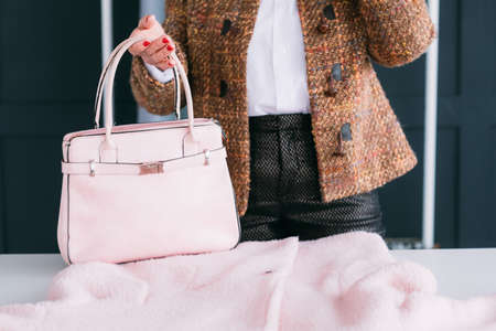 Woman season wardrobe change. Style and elegance. Tweed lady considering trendy pink outfit and bag accessory.