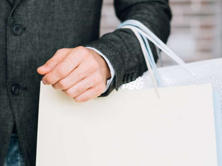 Male fashion store sale. Black Friday. Man with shopping bags. Copy space on ivory paper packet.