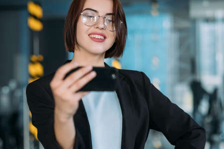 Confident business lady. Office workspace. Beautiful young woman hand on hip taking selfie.