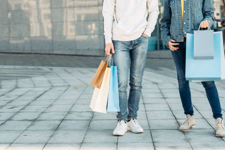 Shopping time. Casual leisure of urban couple. Man and woman with paper bags. Copy space for advertising.