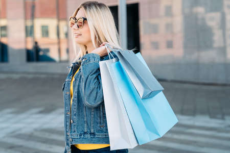 Woman shopping. Blonde female casual leisure. Assortment of paper bags in hands.