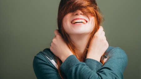 Redhead female expressing joy emotion. Young woman with toothy smile messing hair. Copy space on green background.