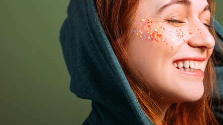 Woman emotion. Happy young female smiling with eyes closed. Glitter freckles makeup. Copy space on green background. Stock Photo