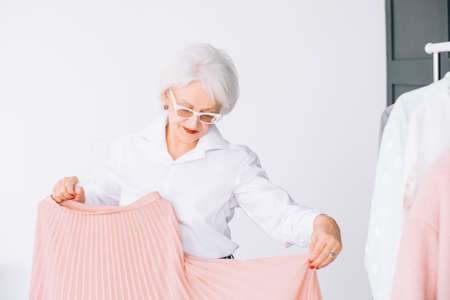 Senior lifestyle. Fashion clothes shopping. Confident elderly lady trying on elegant garment.
