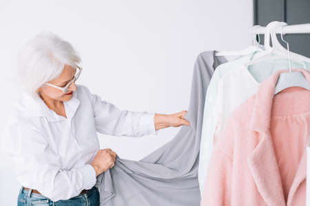 Senior fashion style. Shopping and clothing options. Elderly lady choosing outfit.