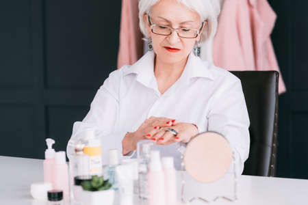 Senior woman hands care. Wrinkled skin beauty products. Aged lady applying cosmetics. Stock fotó