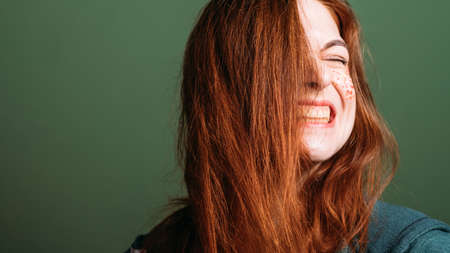 Woman emotion. Facial grimace. Young redhead female with bared teeth. Copy space on green background. Stock Photo
