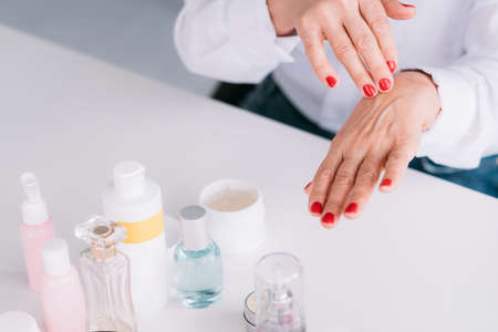 Senior woman hands care. Wrinkled skin beauty products. Aged lady applying care cosmetics. Stock Photo