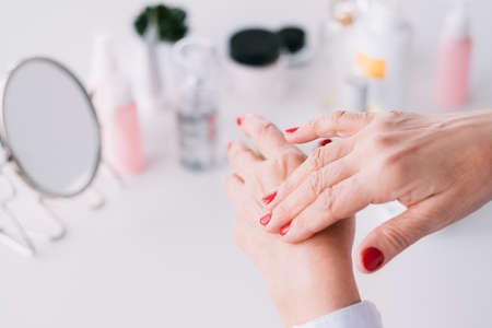 Beauty care senior blogger. Age hand skin products. Elderly lady applying expensive cosmetics.