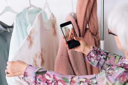 Senior fashion style review. Wardrobe shopping. Elderly lady taking mobile photo while choosing outfit.