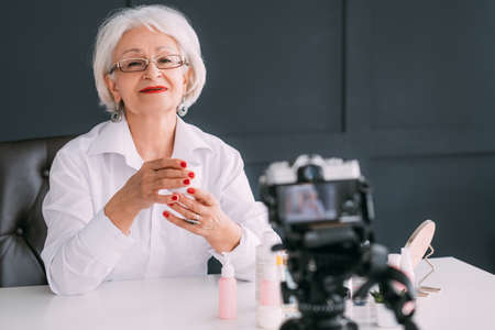 Senior beauty blogger. Successful business woman. Elderly lady making video with care cosmetics around. Stock Photo