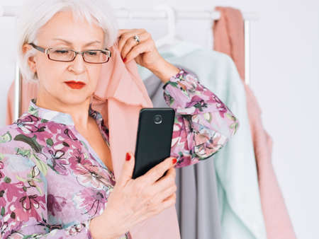 Successful senior woman. Fashion boutique business. Elderly lady taking selfie when analyzing color type.