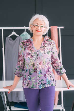 Senior business woman workplace. Stylish fashion showroom. Content trendsetter and coach looking at camera.