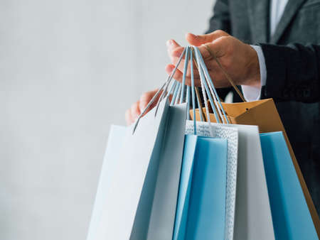 Man in shopping. Casual leisure. Cropped shot with bags variety. Copy space on grey background.