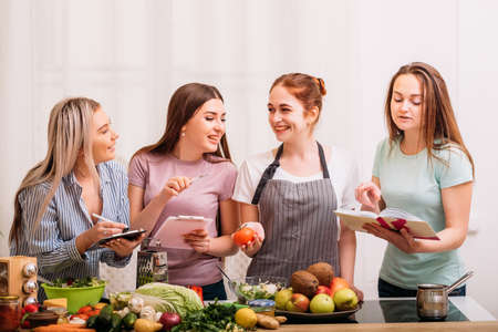 Cooking housewives. Healthy recipes. Dieting with food expert. Excited females discussing organic nutrition.