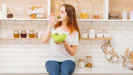 Healthy nutrition. Diet food and female fitness. Young woman eating salad from a bowl sitting on a kitchen counter.