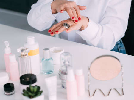 Senior woman hands. Expensive cosmetics review. Elderly lady applying cream with beauty products assortment around.