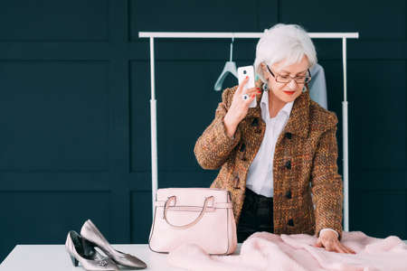 Senior elegant business female. Wardrobe shopping. Elderly lady choosing new outfit considering fashion trends.