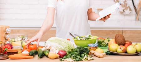 Gesunder Gewichtsverlust und ausgewogene Ernährung. Lebensstil der Frau. Frau mit Rezeptbuch, das Salat zubereitet. Bio-Lebensmittel-Sortiment. Standard-Bild