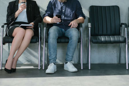 Job interview. Waiting applicants. Coffee and smartphone. Woman and man legs cropped shot.