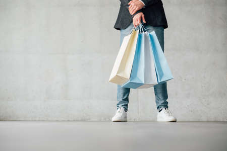 Man shopping. Casual leisure. Male legs in jeans. Paper bags variety in hands. Copy space on grey background. 스톡 콘텐츠
