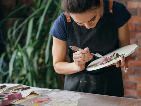Artist workplace. Inspiration. Ceramic artwork in process. Woman in apron with modeling tools working in studio.