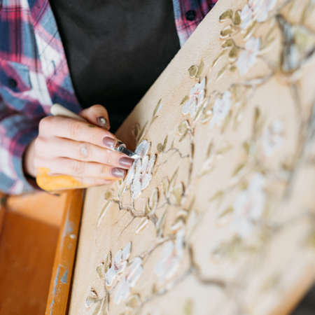 Studio artwork. Floral pattern canvas. Artist at work. Woman painter with modeling tool carving. Stock Photo
